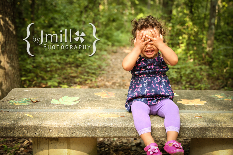 baby girl playing peek a boo on bench