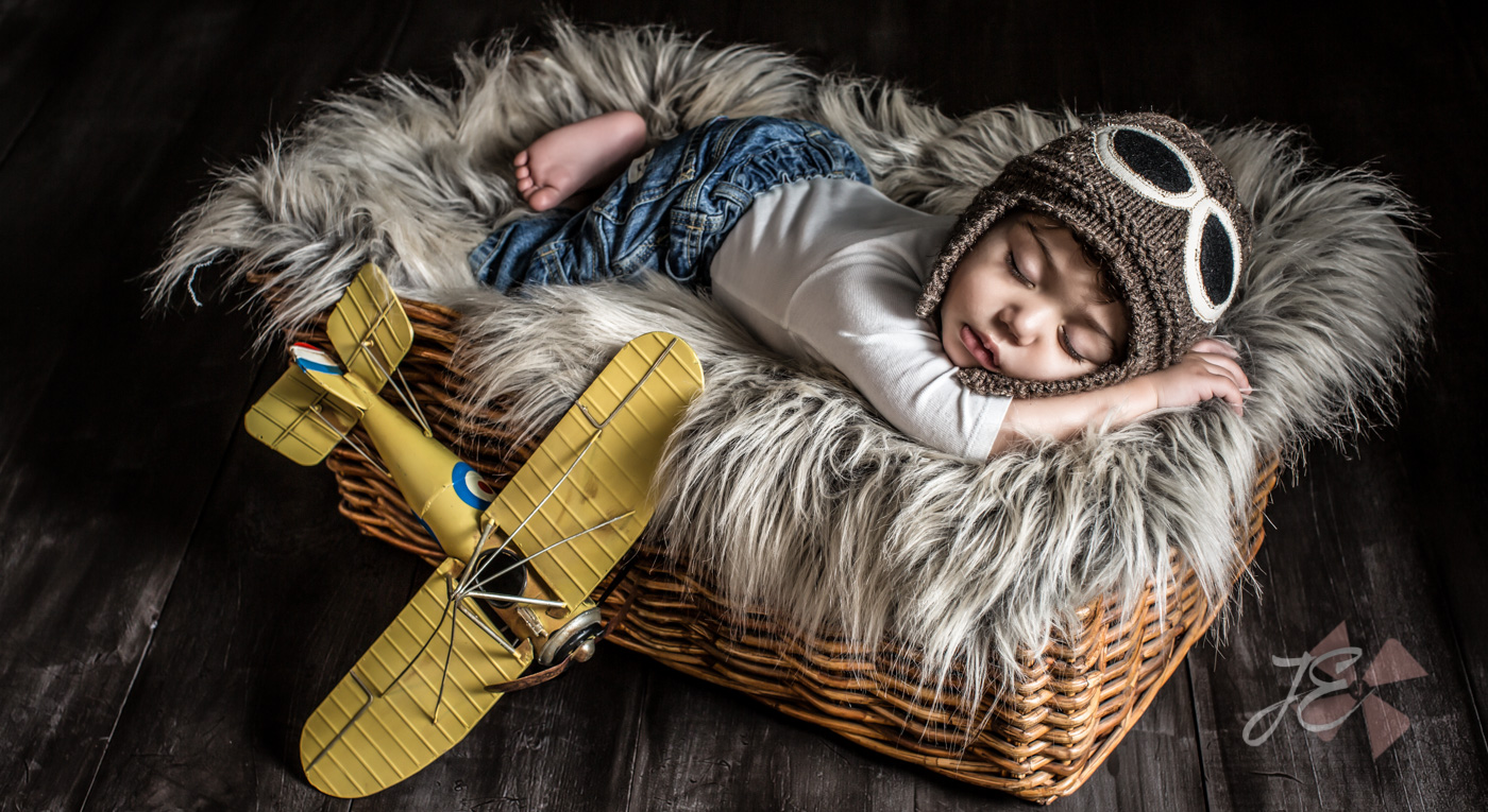 Whimsical Newborn Portrait of a baby boy pilot with his yellow toy airplane