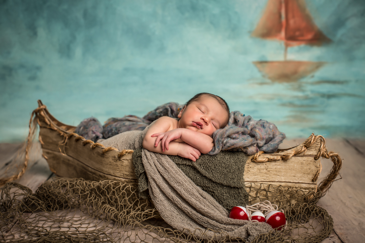 Whimsical portrait of precious newborn baby boy in boat by ocean, by Jenn Elisabeth Photography in Woodbridge Virginia