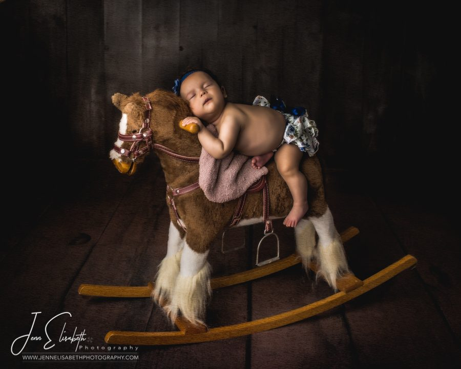 Newborn Baby Girl on Rocking Horse