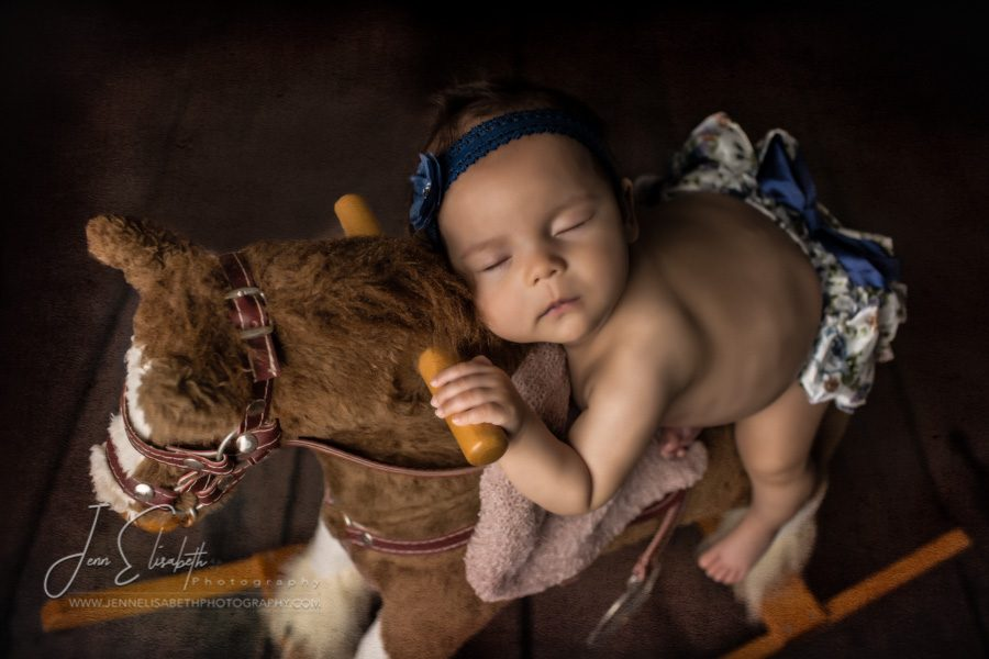 Portrait of baby girl on rocking horse