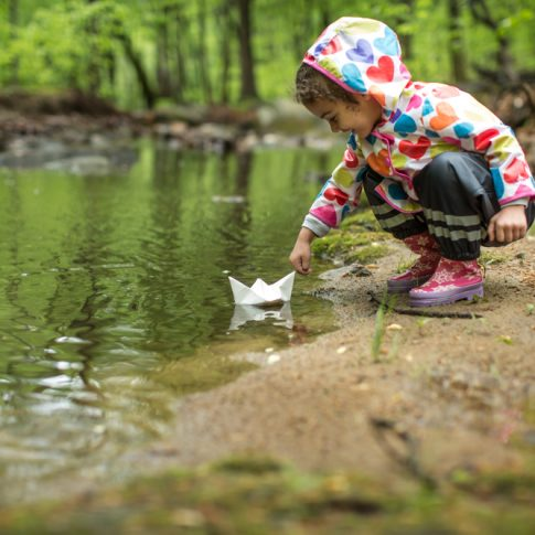 Little girl in the rain with her paper boat