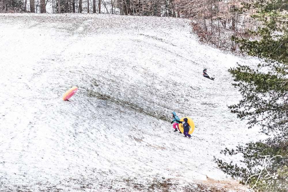 Girls chasing dounut innertub up a snowy hill